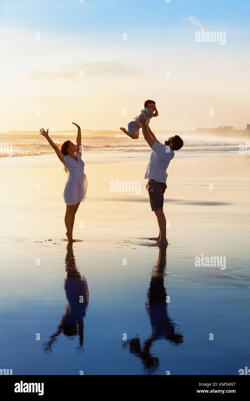 Vater werfen hoch in der Luft baby Sohn, Mutter springen durch Wasser Pool. happy family Gehen Sie mit Spaß durch Stockfoto
