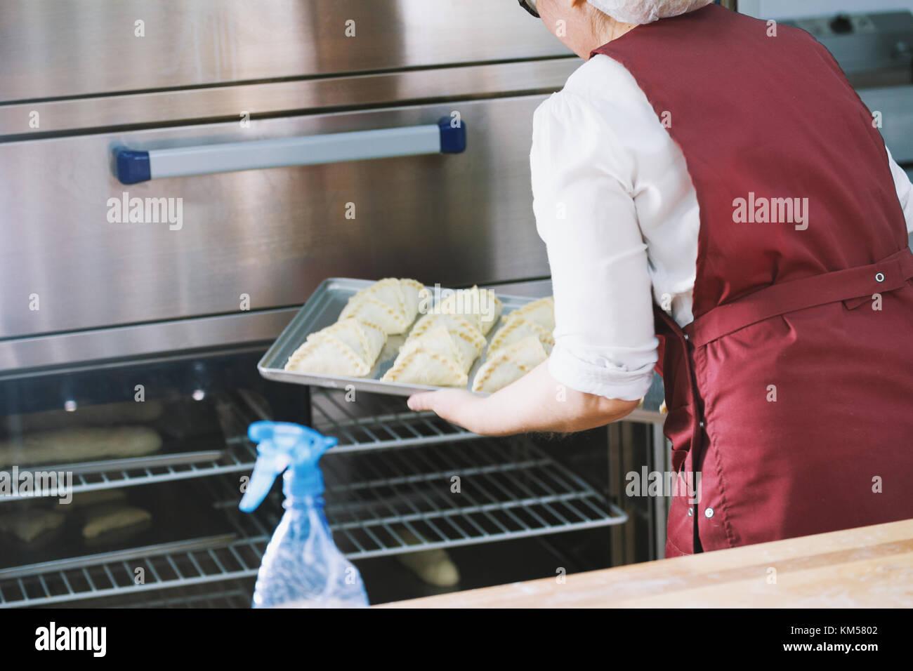 Frau setzt rohes Fleisch Kuchen im Ofen Stockbild