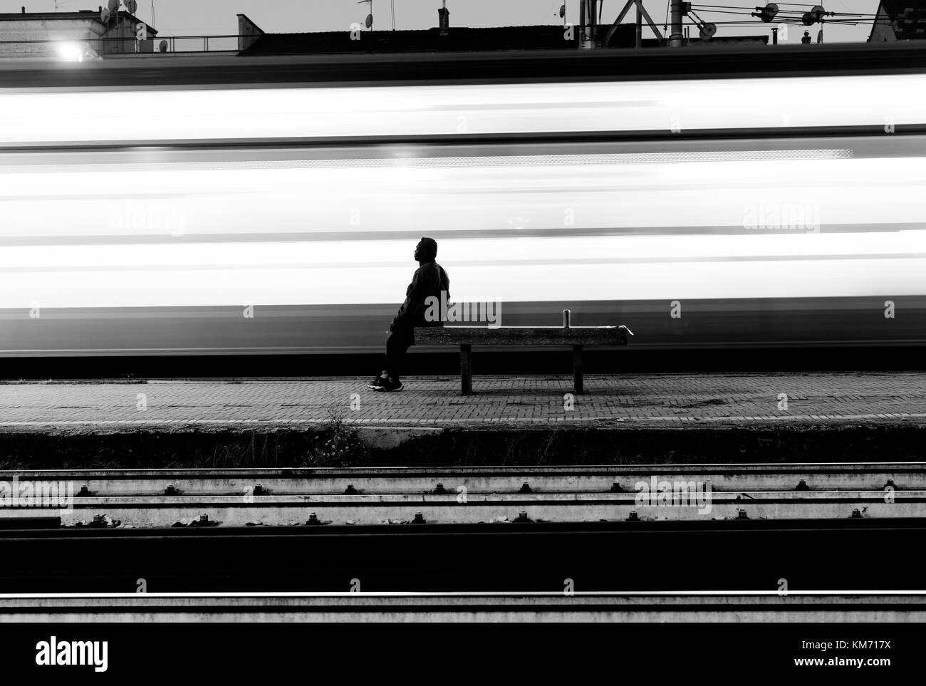 Der Mensch in der Nähe einer racing Zug, hinterlässt Spuren des Lichts Stockbild