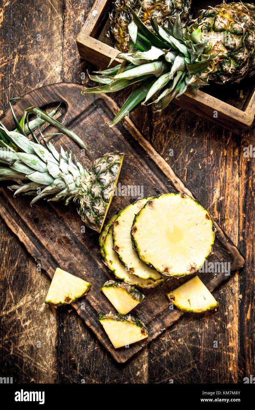 In Scheiben geschnittene frische Ananas. Auf dem hölzernen Hintergrund. Stockbild