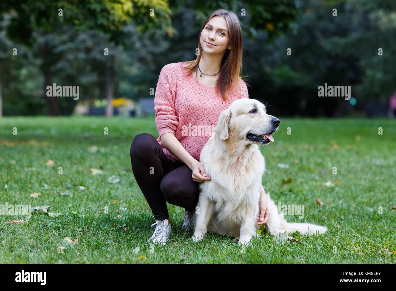 Foto von Mädchen umarmt Hund auf dem grünen Rasen Stockbild