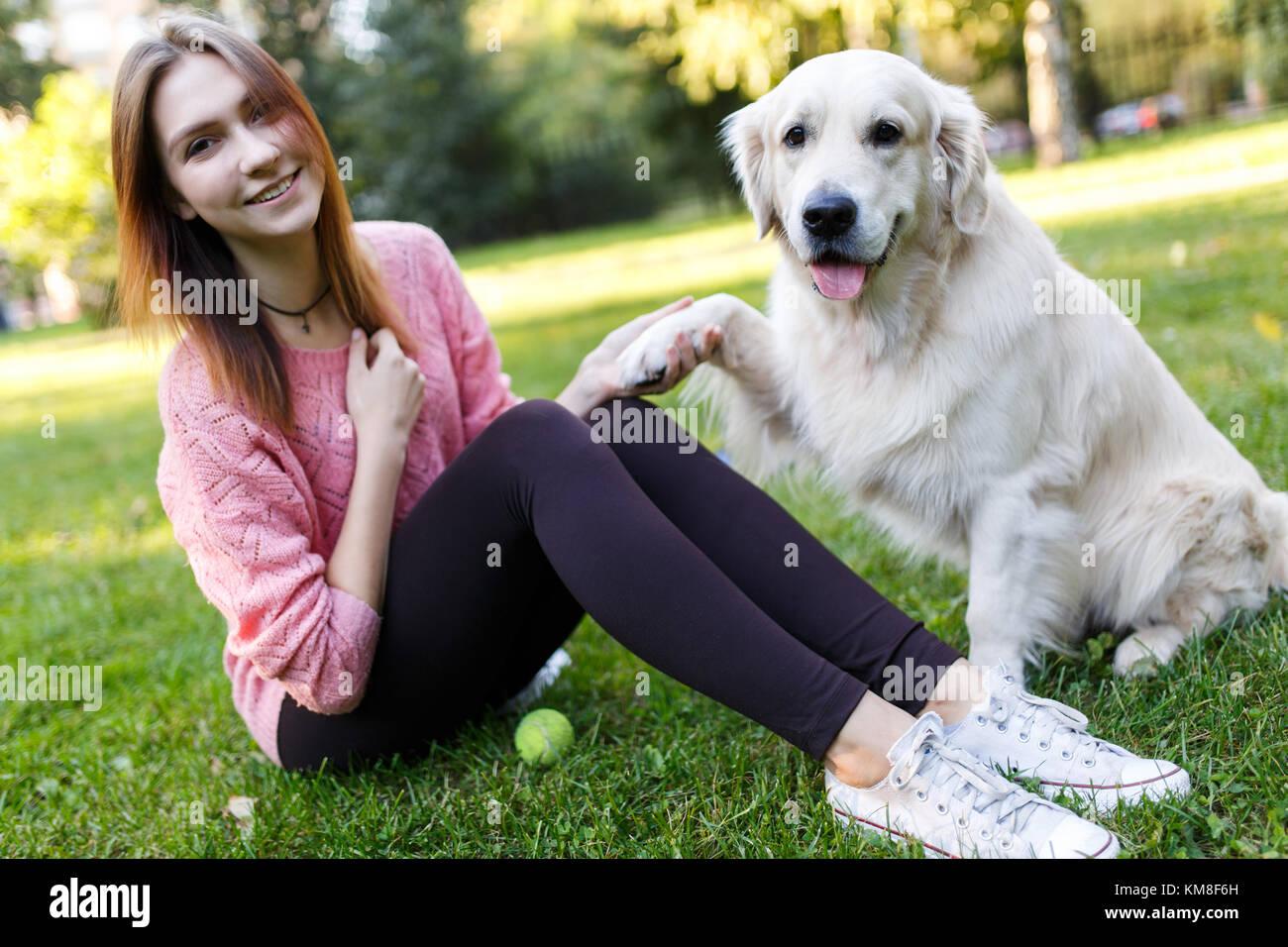Foto von Brünette mit Kugel und Hund sitzen auf Rasen Stockbild