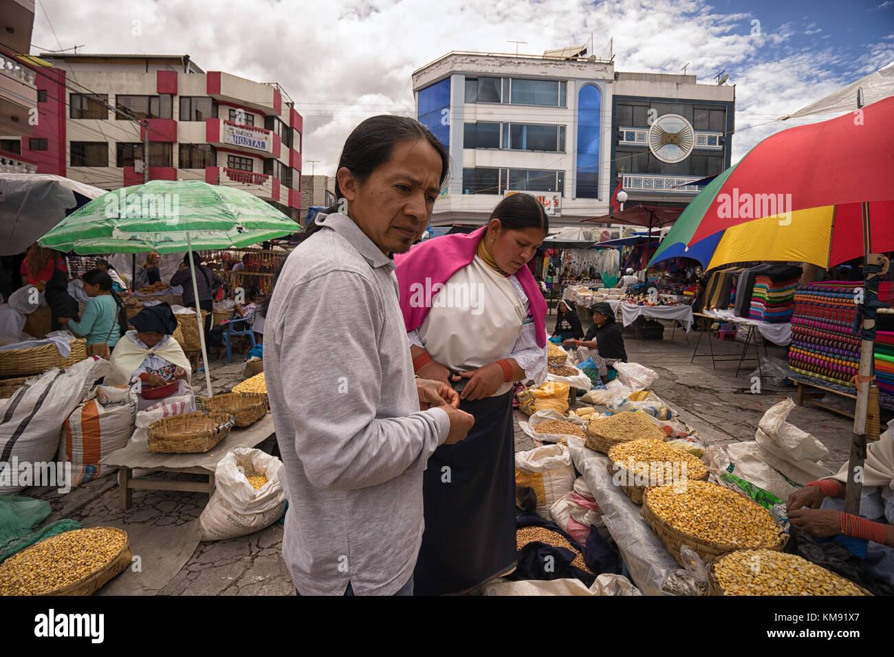 Otavalo, Ecuador - Dezember 2, 2017: indigene Mann und Frau Einkaufen in der Samstag im freien Handwerker- und Bauernmarkt Stockbild