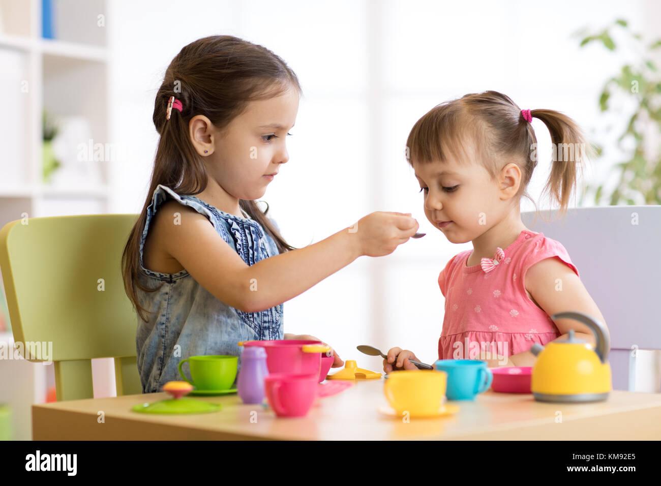 s e kleine kinder spielen mit k chenutensilien beim sitzen am tisch zu hause oder im. Black Bedroom Furniture Sets. Home Design Ideas