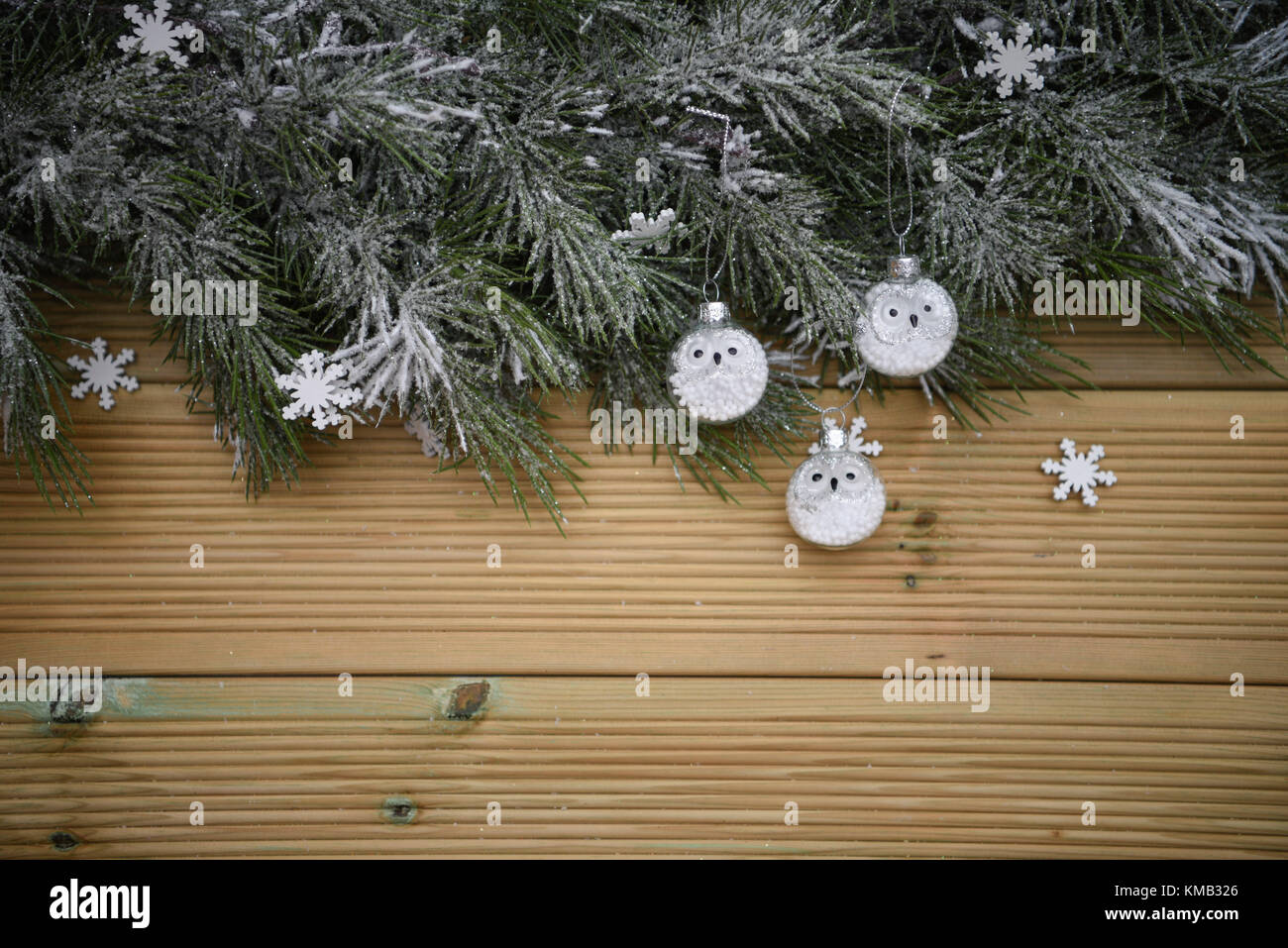 Wintersaison Weihnachtsbaum-girlande mit Schnee und mit rustikalen natürlichen Holz Hintergrund und hängende Stockbild