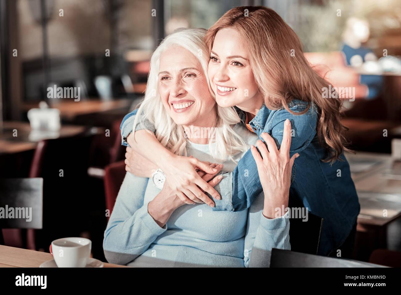 Positive senior Frau lachend während ihrer Enkelin umarmte ihre Stockbild