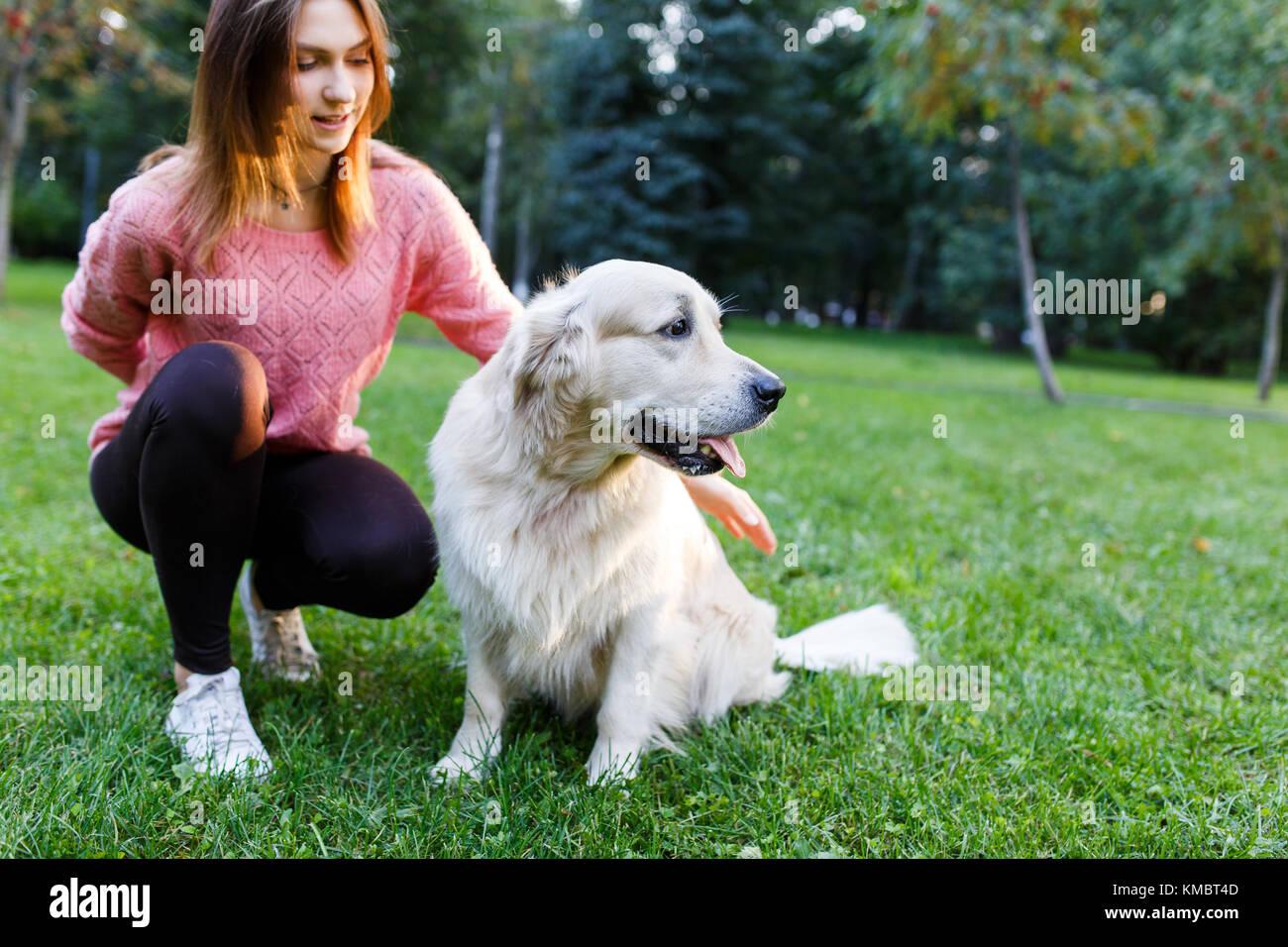 Foto von Brünette mit Labrador liegen auf dem Rasen im Sommer Park Stockbild