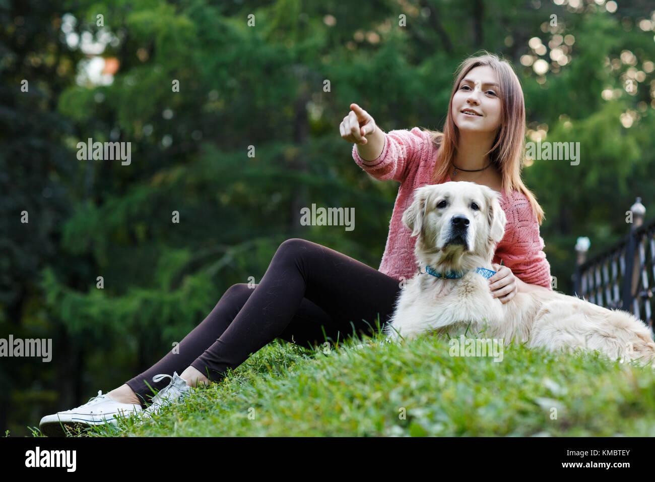 Foto von unten der Frau nach vorn zeigen neben Hund auf dem grünen Rasen Stockbild