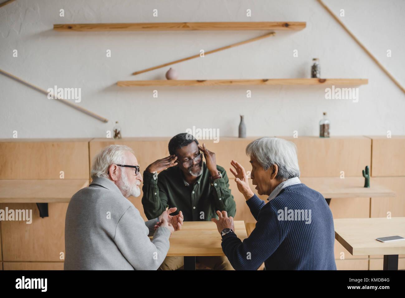 Ältere Freunde in diskutieren Stockbild
