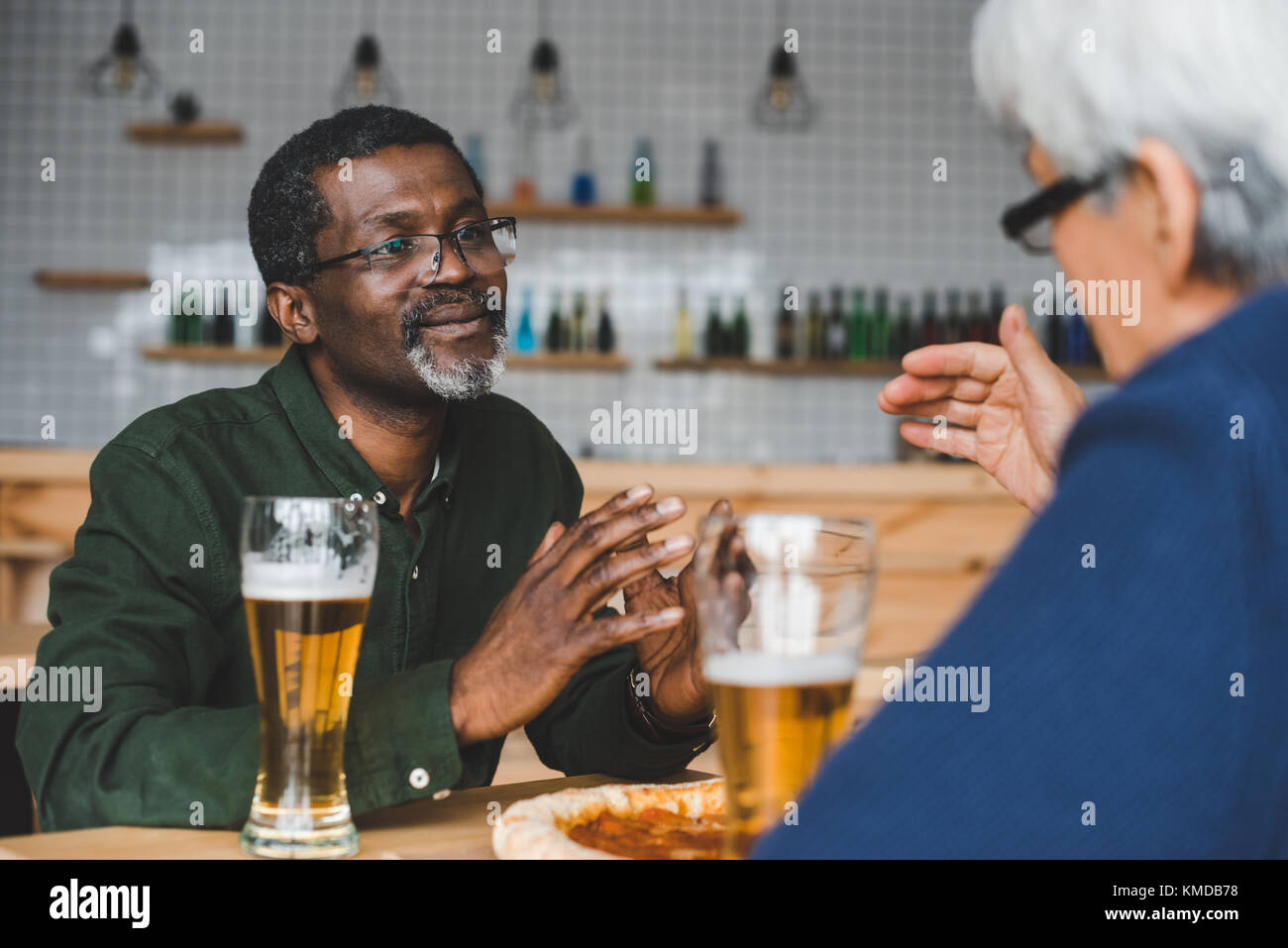 Ältere Freunde Diskussion in bar Stockbild