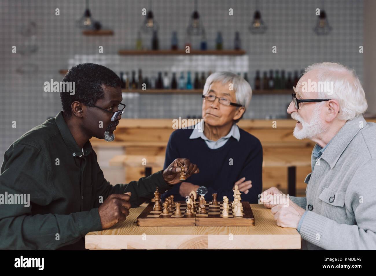 Senior Freunden Schach spielen Stockbild