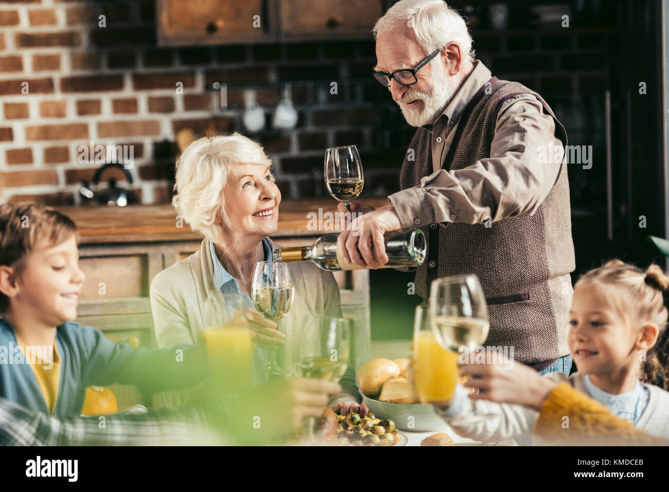 Ältere Menschen gießen Wein für Frau Stockbild