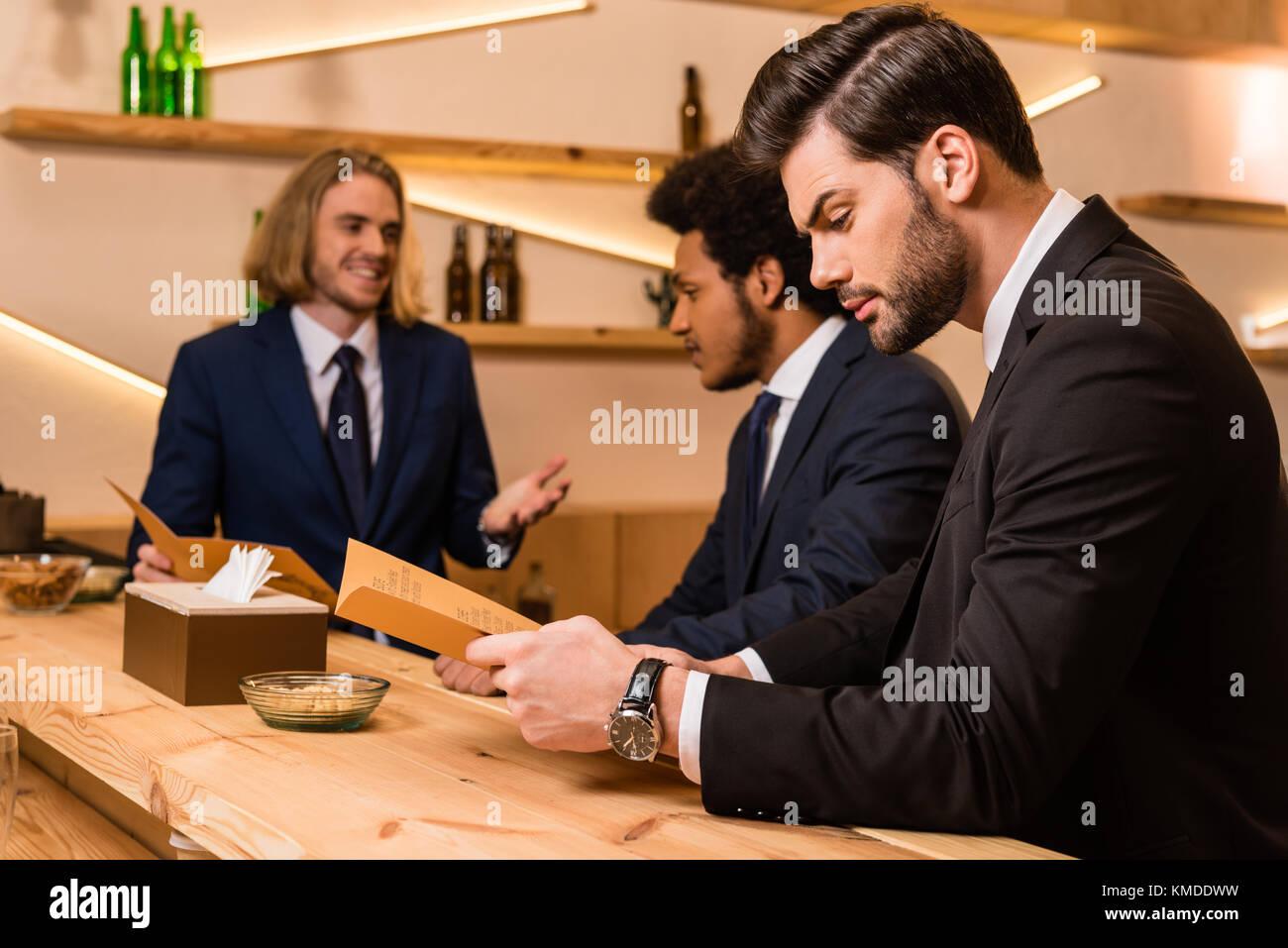 Geschäftsleute mit Menü in bar Stockbild