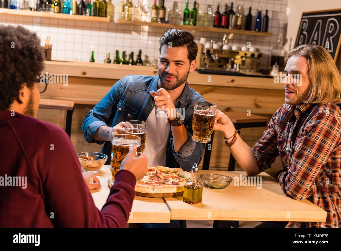 Freunde mit Pizza und Bier in der Bar Stockbild