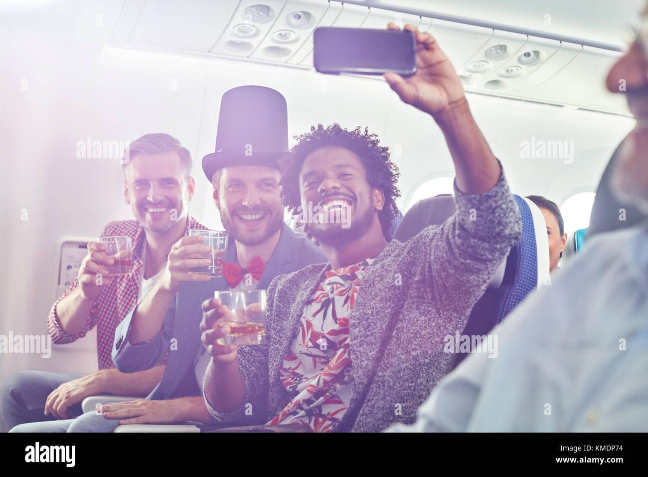 Begeisterte junge männliche Freunde mit Kamera Handy trinken und selfie auf Flugmodus Stockbild