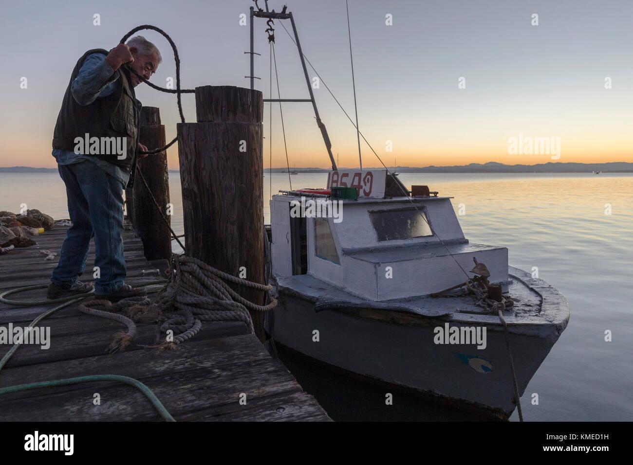Garnelen Fischer stehen auf Pier in der Nähe von Boat bei Sonnenuntergang, China Camp, Kalifornien, USA Stockbild