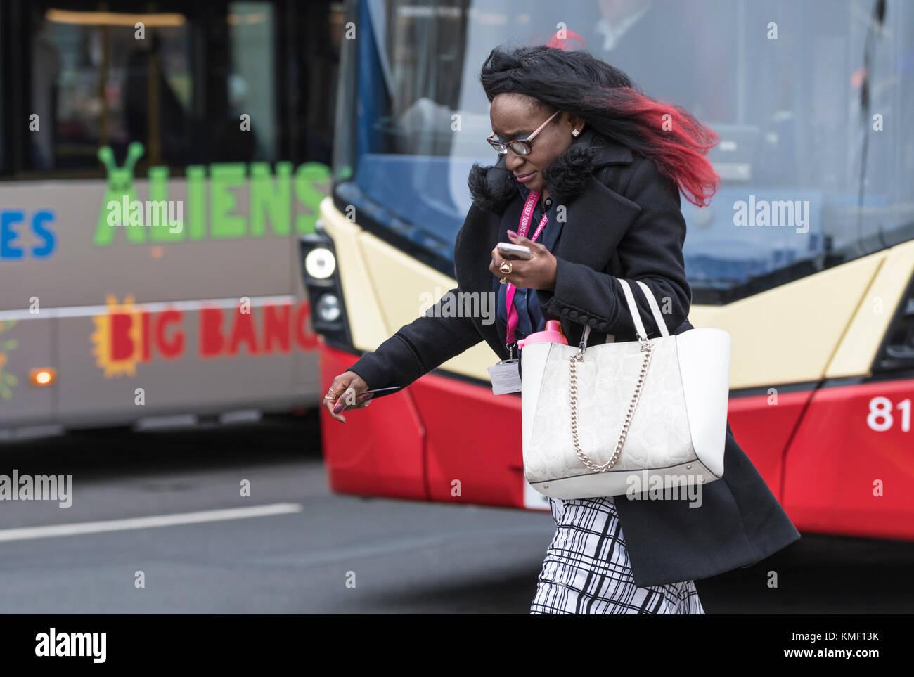 Schwarze Frau elegant gekleidet, die eine schicke Handtasche, schnell gehen mit Zuversicht in das VEREINIGTE KÖNIGREICH. Stockbild