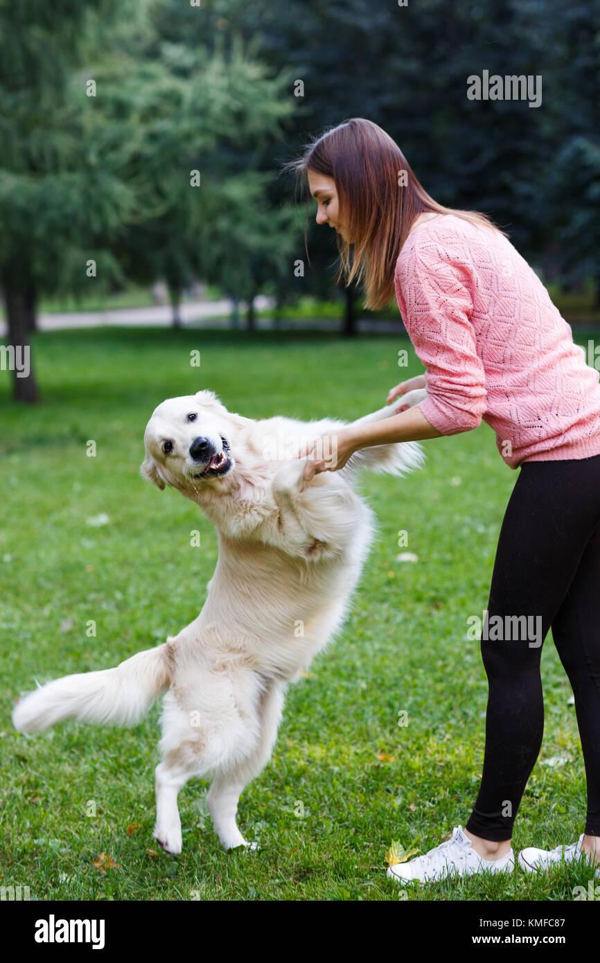 Bild der Mädchen, dass Hund durch die Vorderpfoten auf grünen Rasen Stockbild