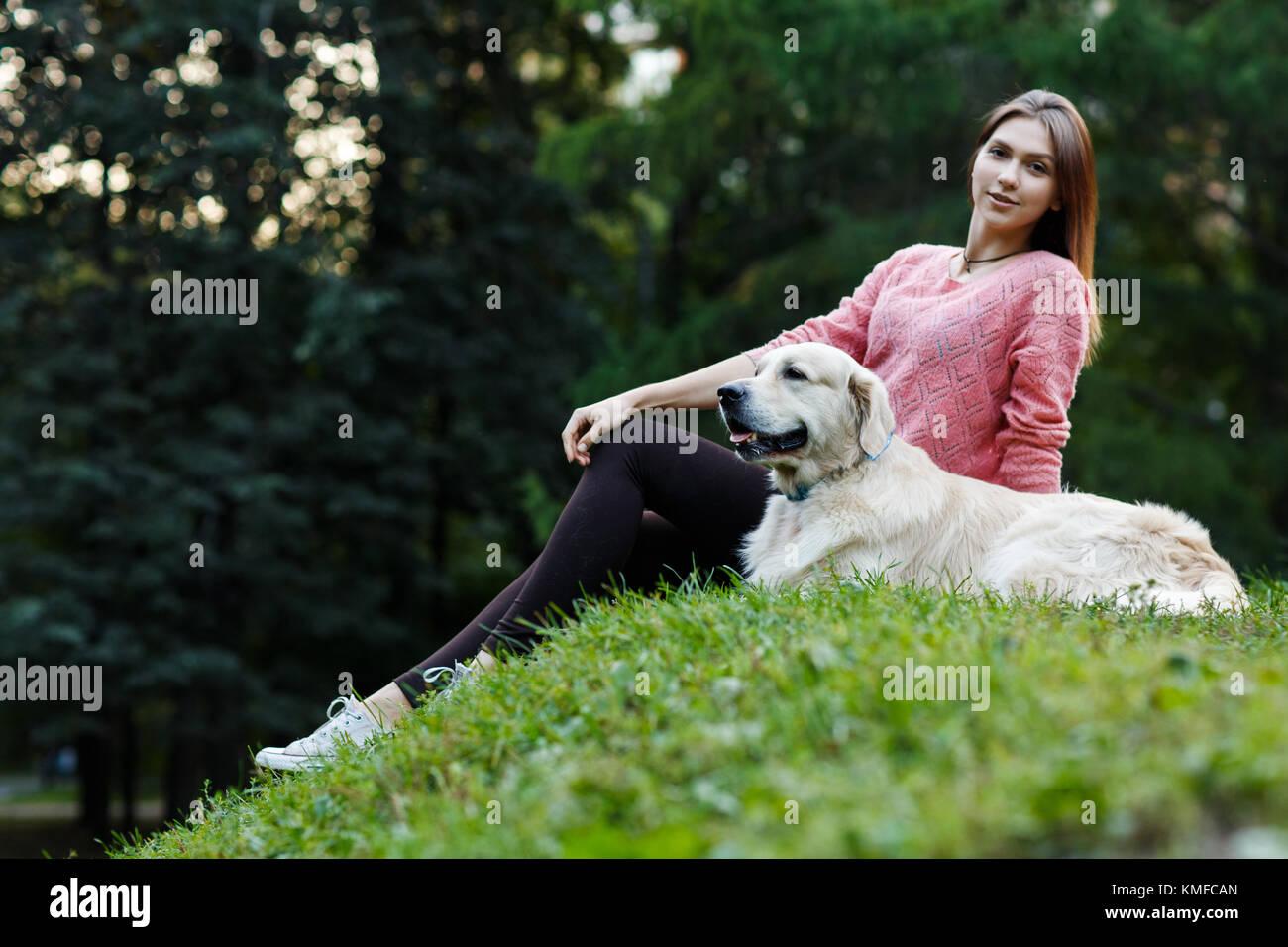 Foto von Mädchen sitzen mit Hund auf dem grünen Rasen im Sommer Tag Stockbild