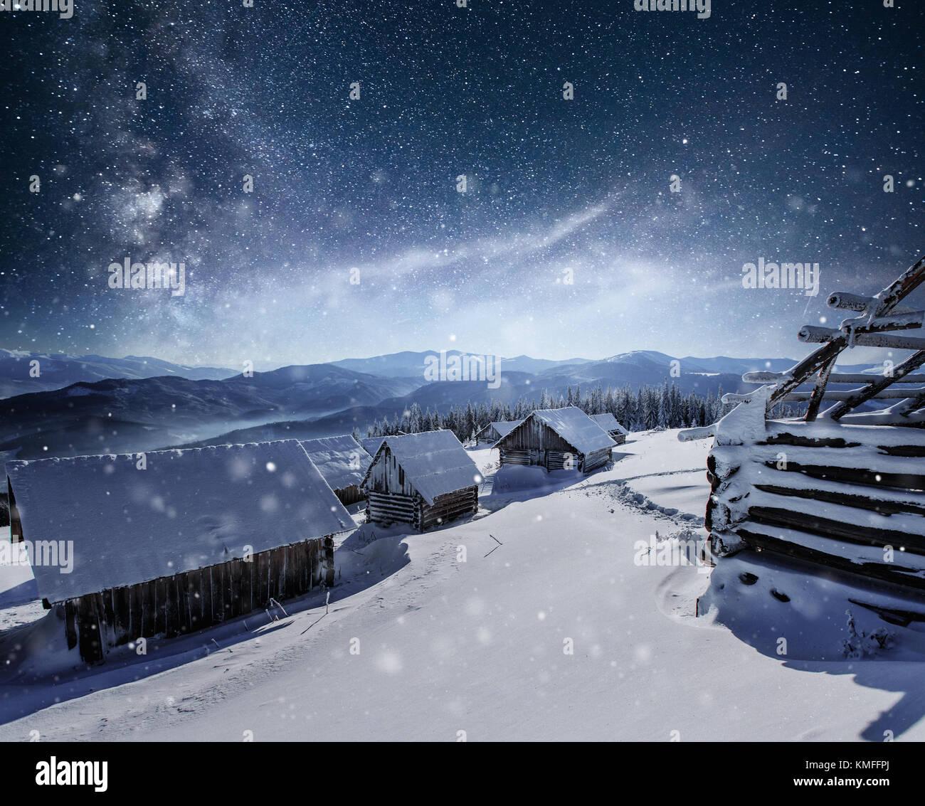 Nacht mit Sternen. Weihnachten Landschaft. Holz- Haus im Bergdorf ...