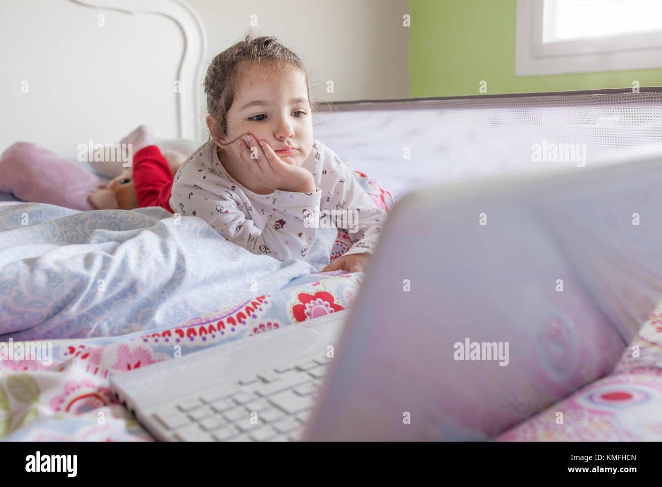 Kleines Mädchen im Bett lag und sich Zeichentrickfilme mit einem Laptop in seinem Schlafzimmer. Sie sieht unterhalten Stockbild