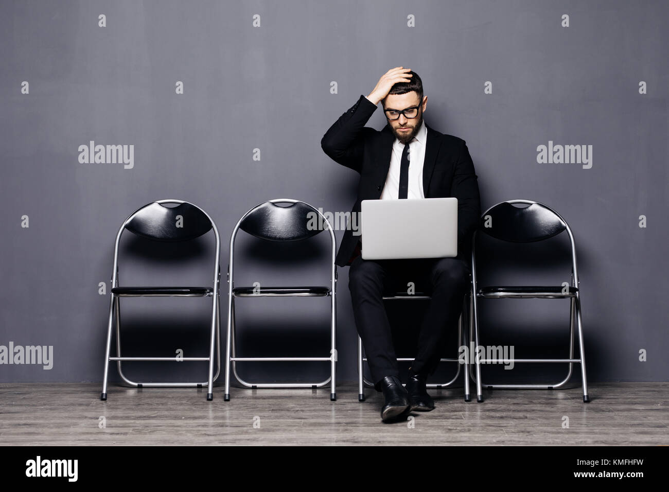 Junger Mann in Anzug sitzen auf Stuhl mit Laptop und warten auf Job Interview Stockbild