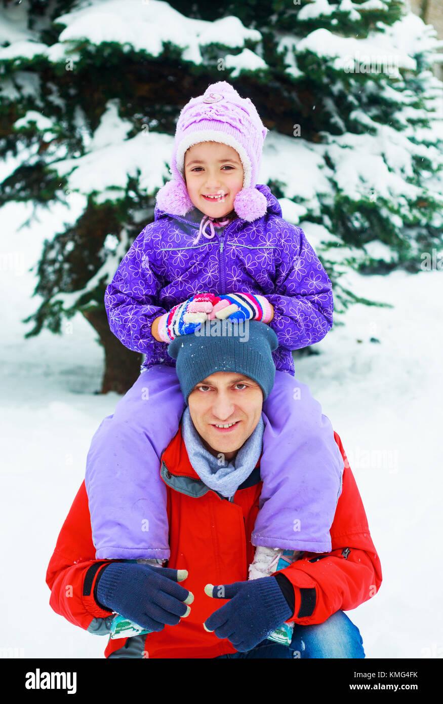 Glückliche junge Vater mit seiner Tochter outdoor im Winter Park Stockbild