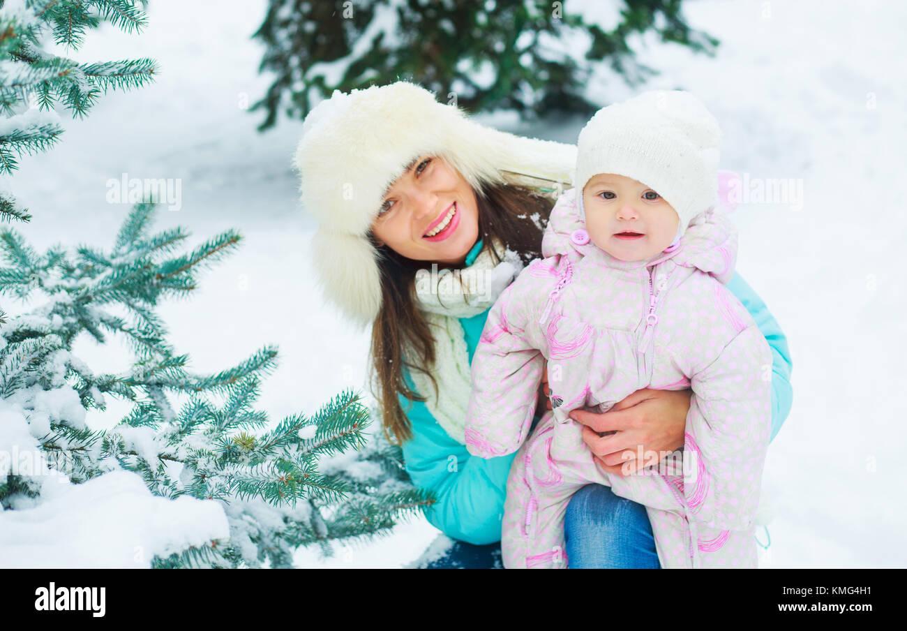 Glückliche junge Mutter und Tochter outdoor im Winter parik Stockbild