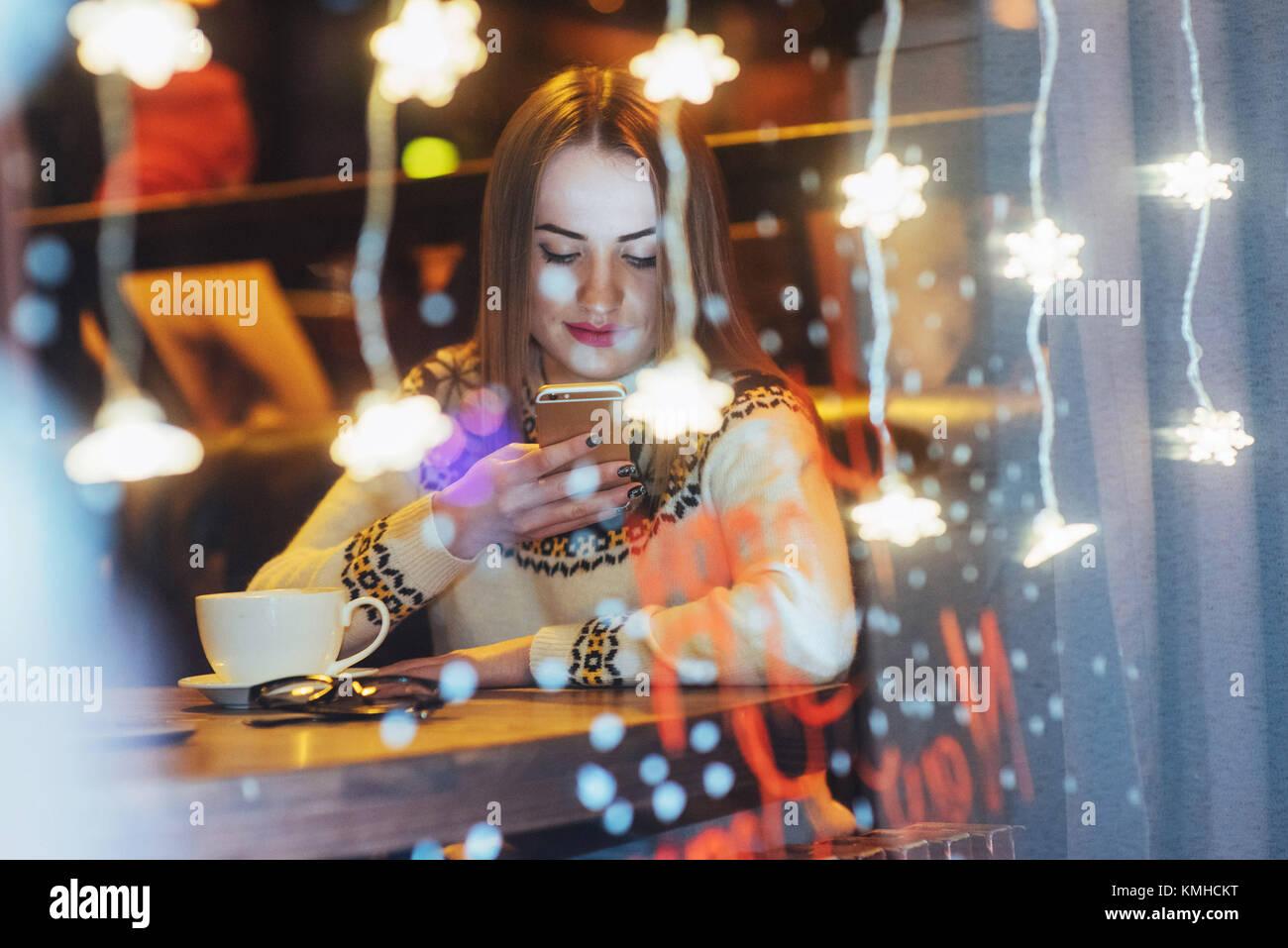 Junge schöne Frau sitzen im Café, Kaffee zu trinken. Magischen Schneefall-Effekt. Weihnachten, Neujahr, Stockbild