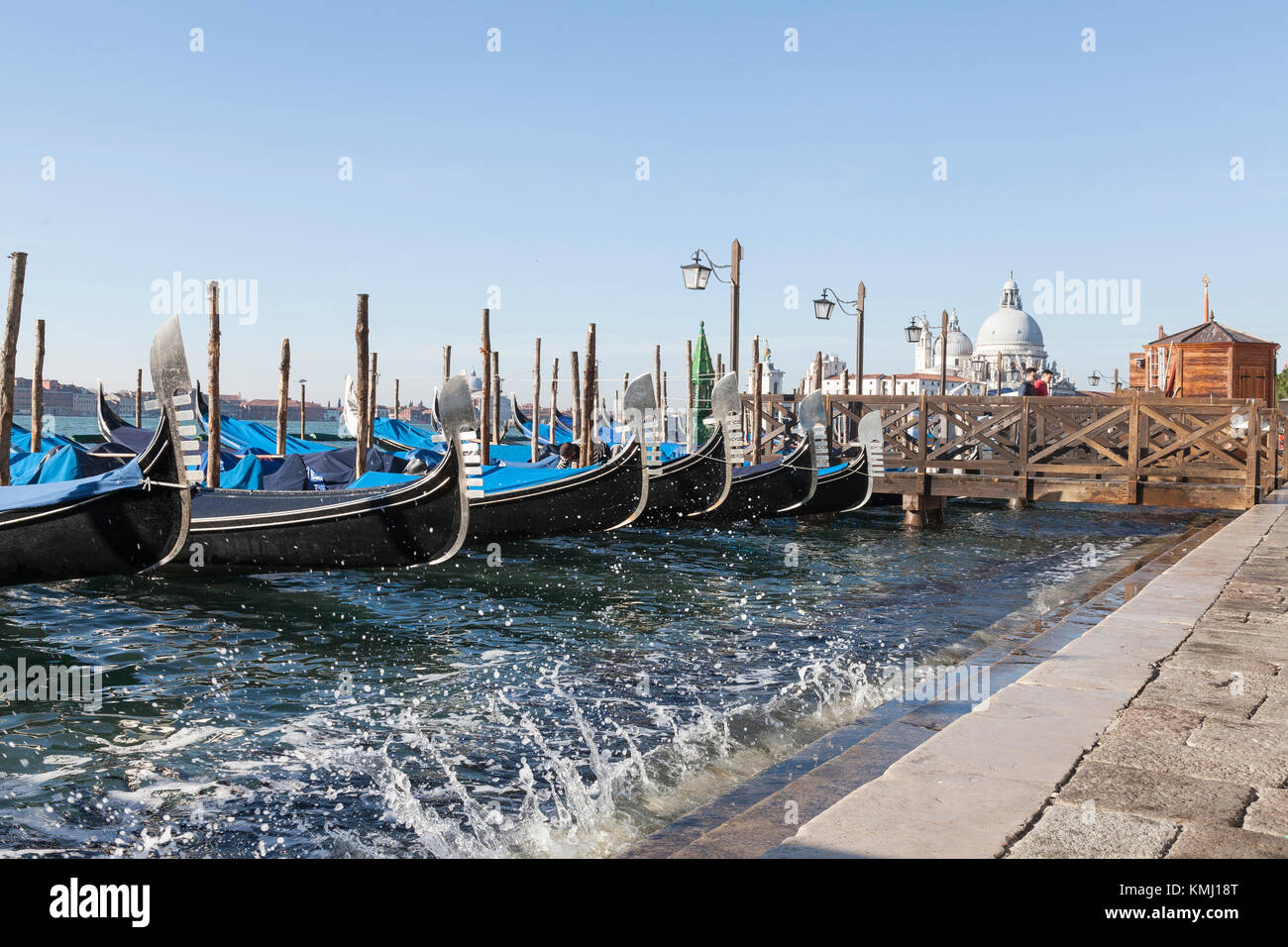 Gondeln an San Marco Reiten hoch im Wasser auf einem Acqua Alta Tide mit Splash und Blick auf Baslica di Santa Maria della Salaute, Venedig, Italien Stockfoto