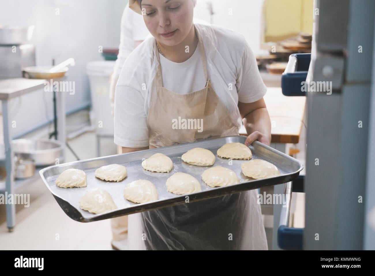 Cook setzt Kuchen in den Ofen zum Backen Stockbild