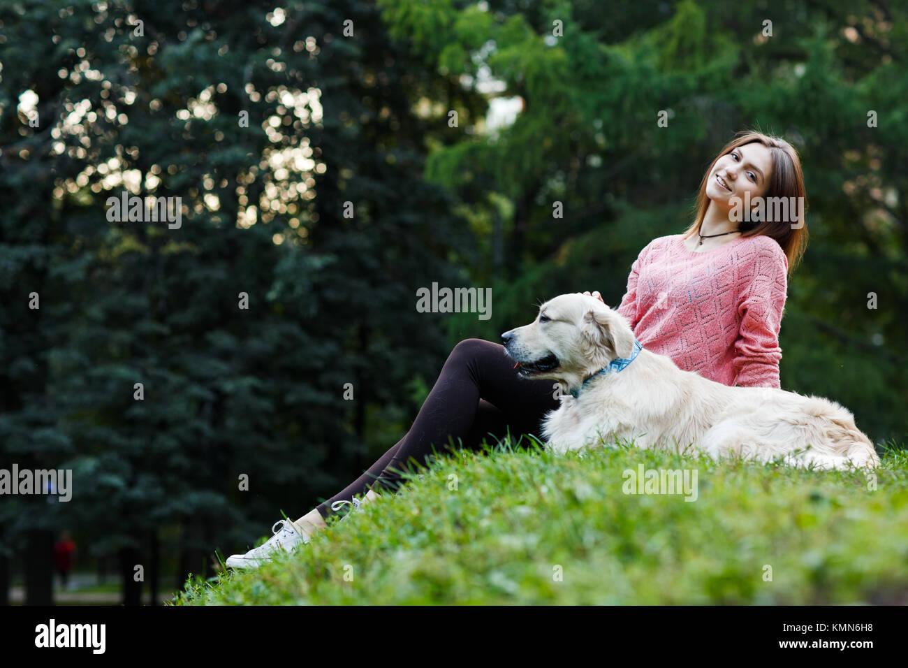 Foto von unten der sitzende Frau mit Hund auf dem grünen Rasen Stockbild
