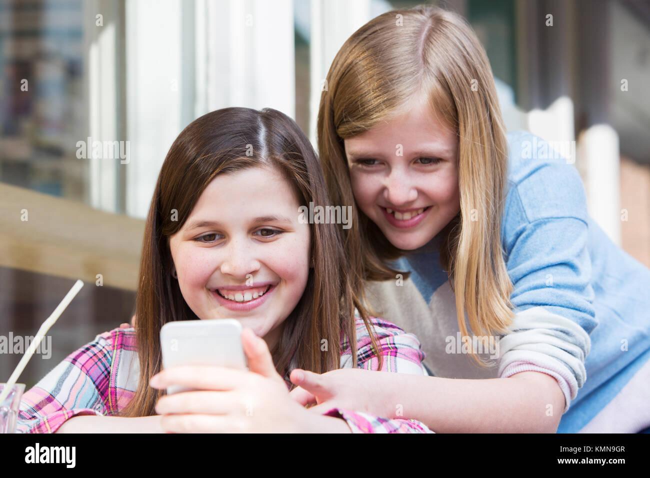 Zwei junge Mädchen im Cafe lesen SMS auf Handy Stockbild