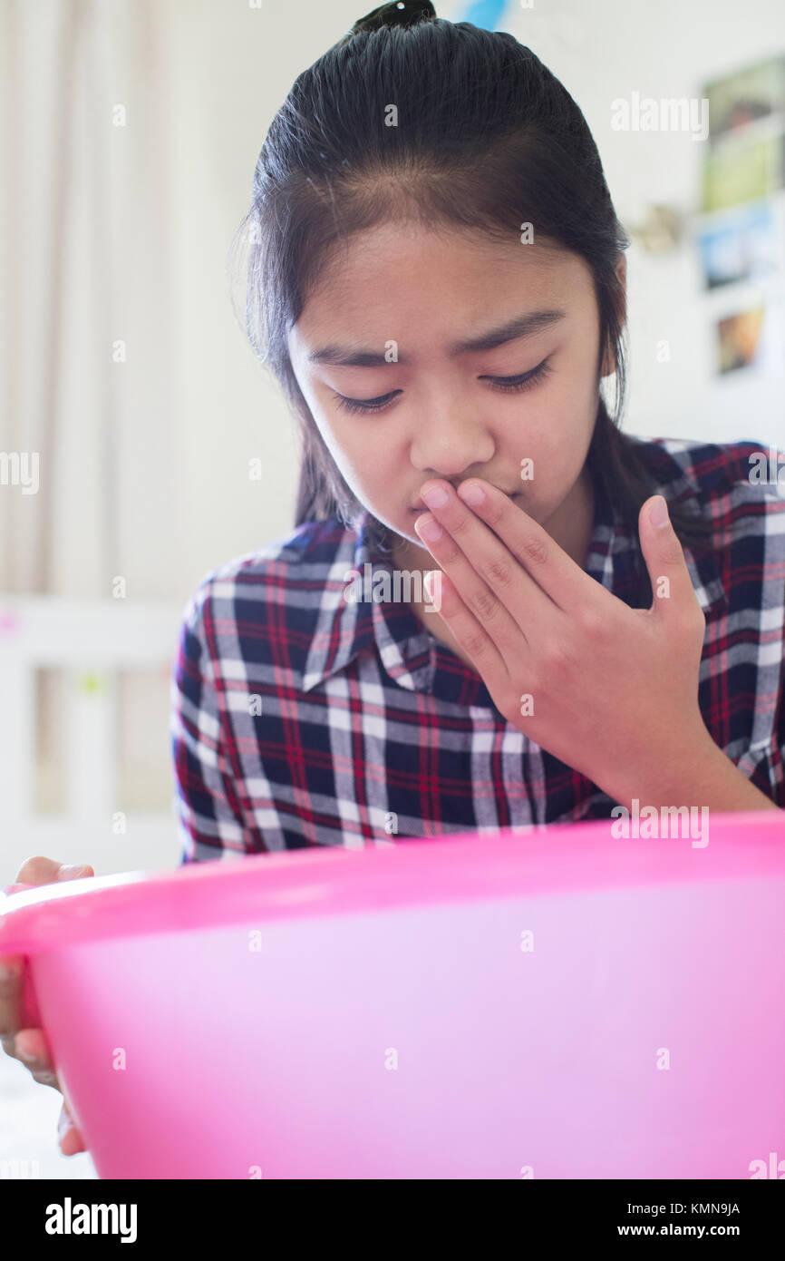 Junges Mädchen sitzt auf dem Bett zu Hause Gefühl ekelerregend Stockbild