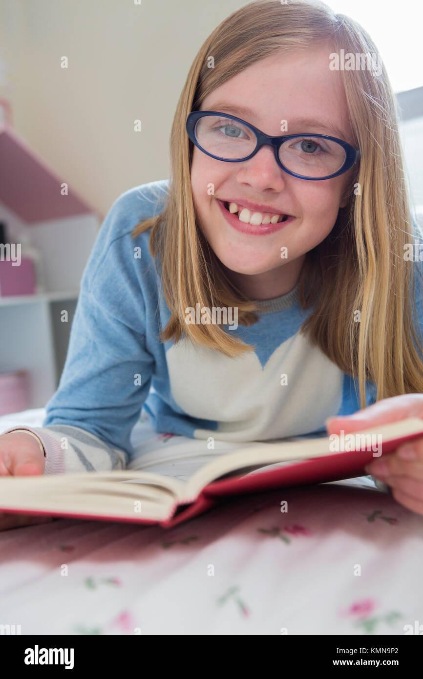 Junges Mädchen auf Lesebuch Bett liegend Stockbild
