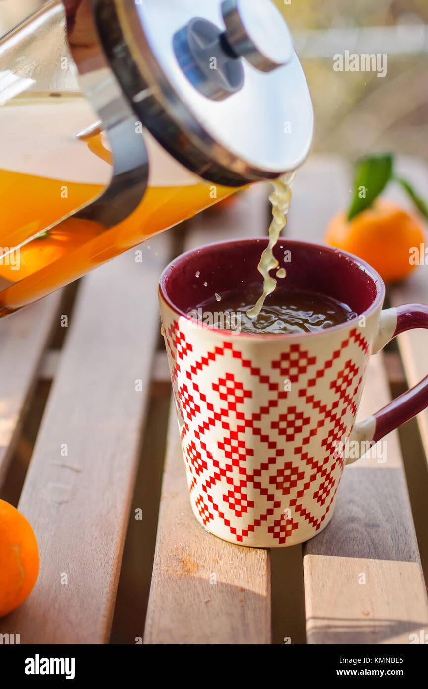 Gießen tangerine Kaffee in die Tasse auf hölzernen Tisch Stockbild