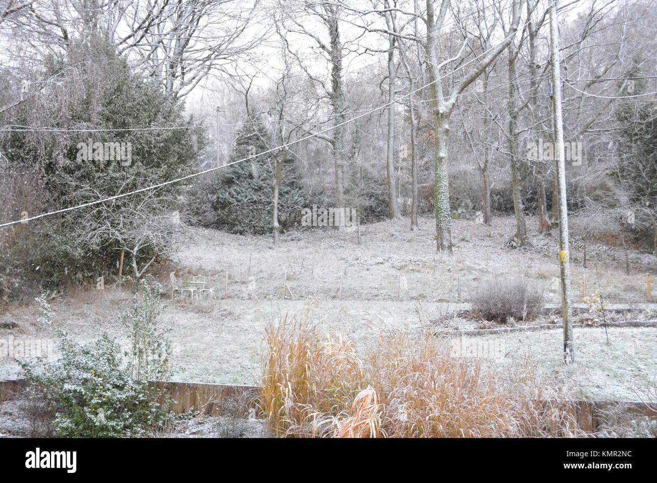 Großen abfallenden Garten im Winter mit einer leichten Schneedecke auf dem Rasen Sträucher Bäume Stockbild