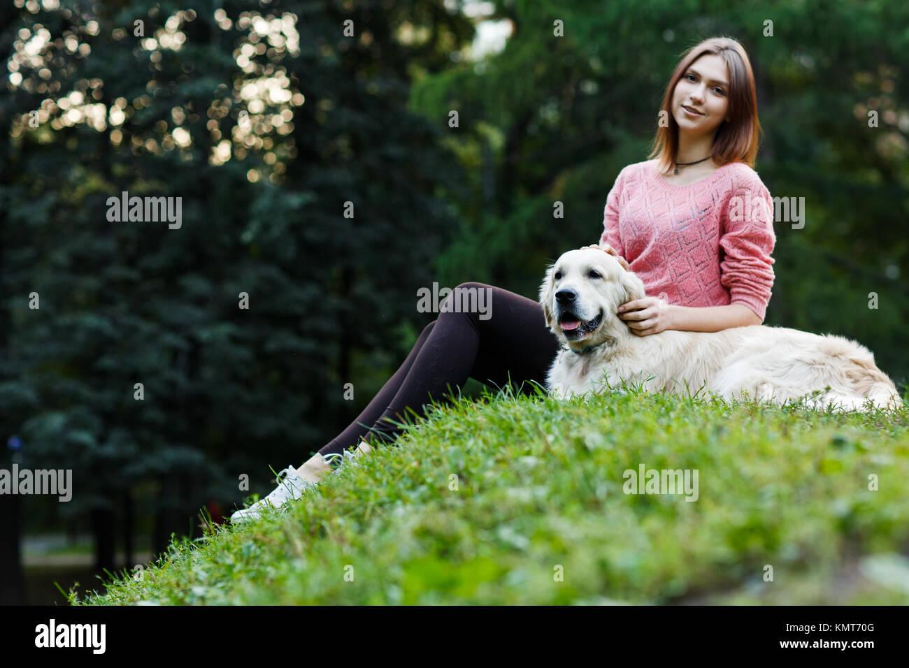 Foto von unten der Brünette sitzen mit Hund auf dem grünen Rasen Stockbild
