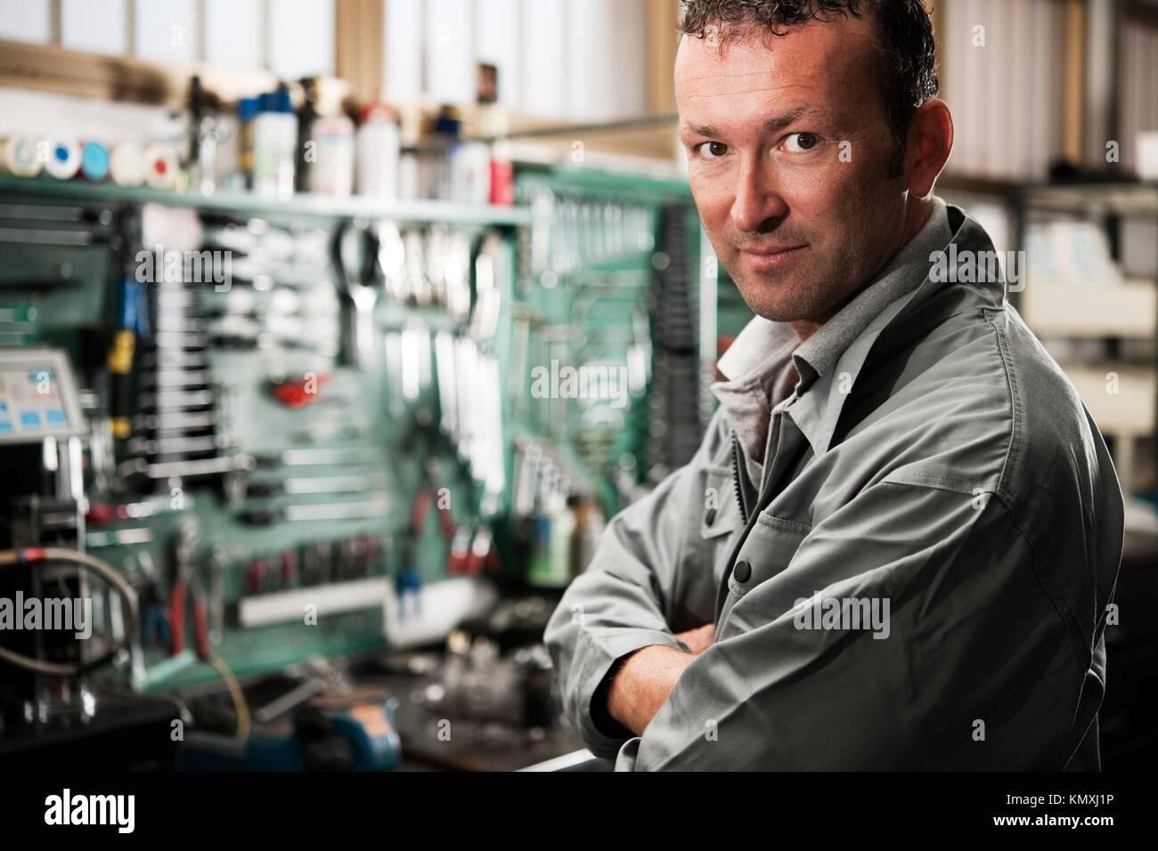 Close-up mit einem lächelnden Mechaniker innerhalb seiner Werkstatt Stockbild