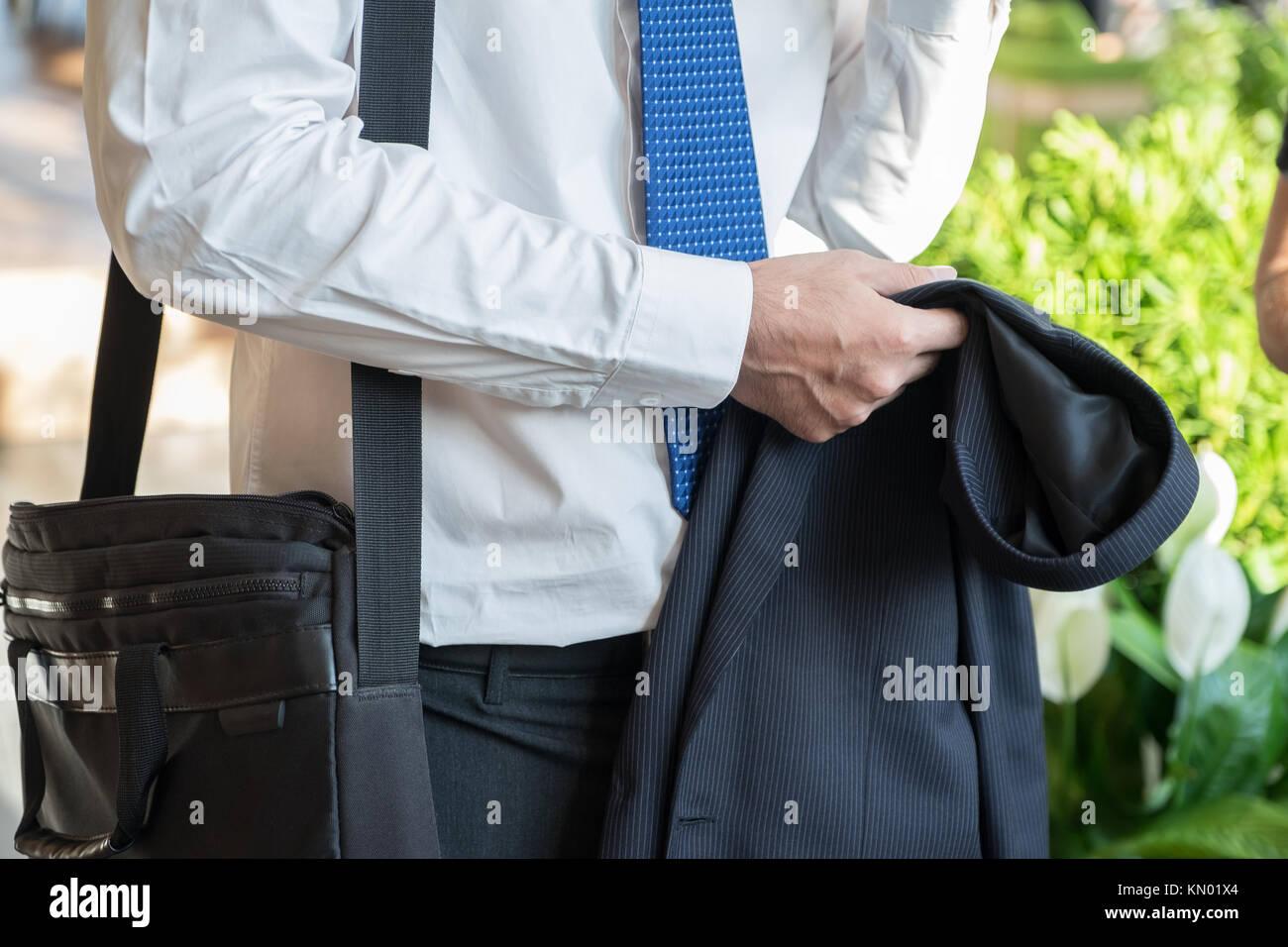 Unternehmer nehmen Anzug aus und sprechen mit Freundin nach der Arbeit im Korridor Bürogebäude, nach der Arbeit Stockfoto
