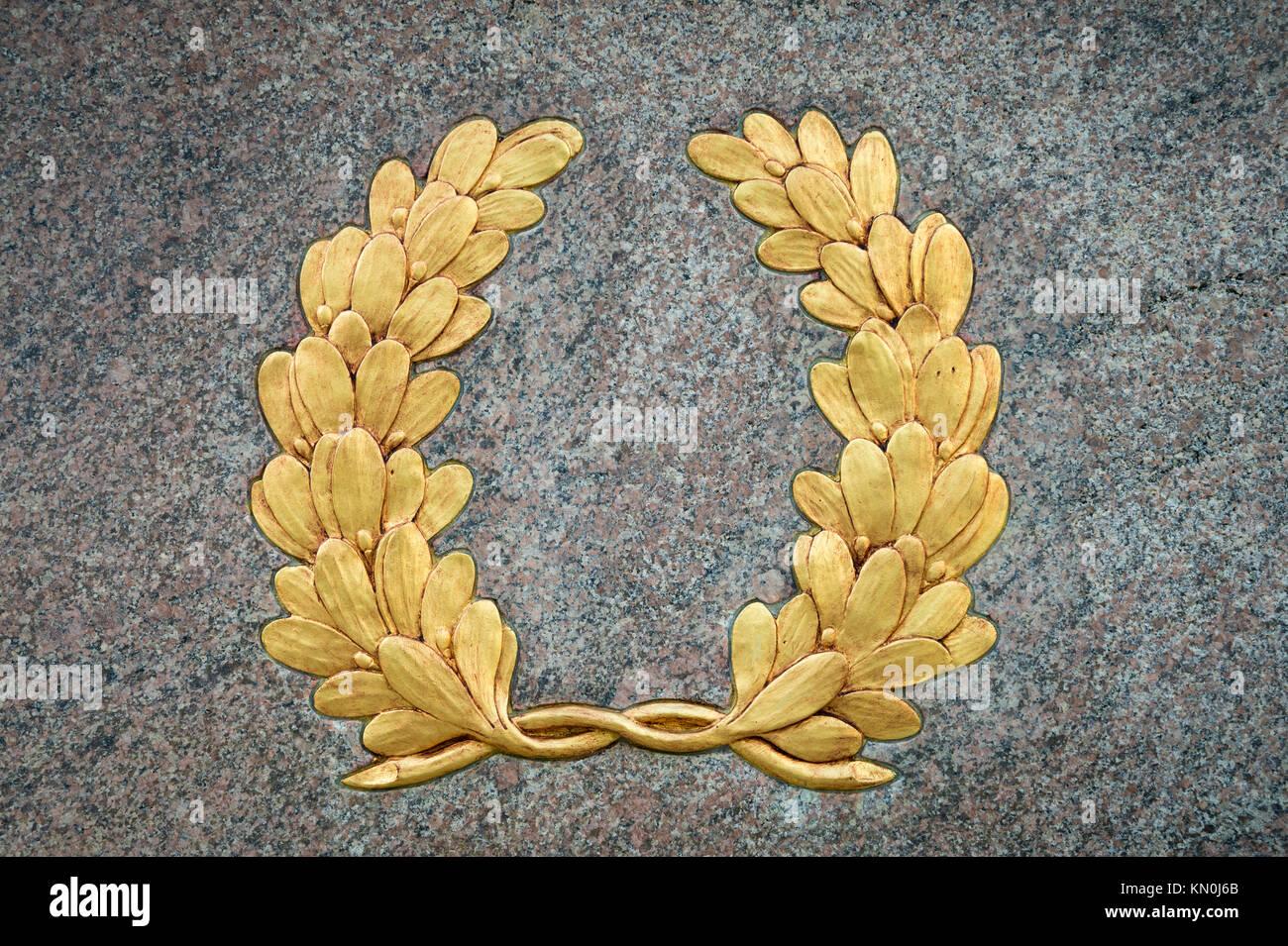 Klassische Lorbeerkranz Symbol mit Vintage Gold leaf detail auf strukturierte Relief gegen einen glatten grauen Stockbild