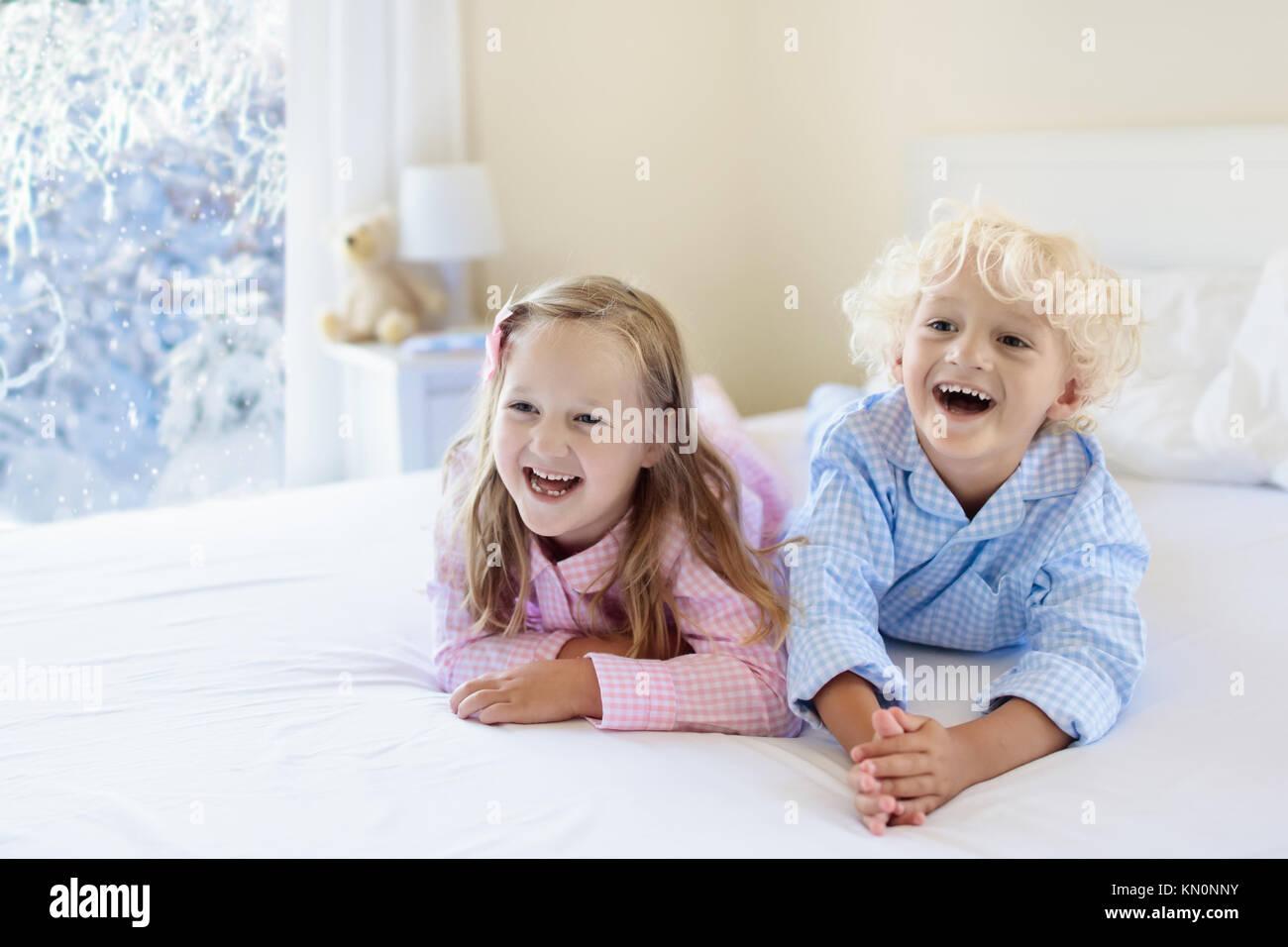 Kinder im Bett der Eltern im Winter. Kinder aufwachen in Weiß ...