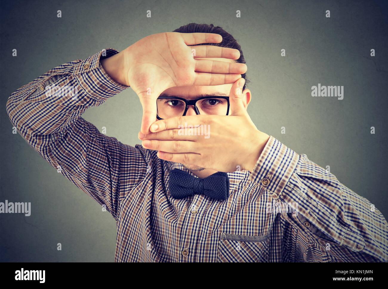 Ernster Mann, einen Rahmen mit seinen Händen an Kamera suchen Stockfoto
