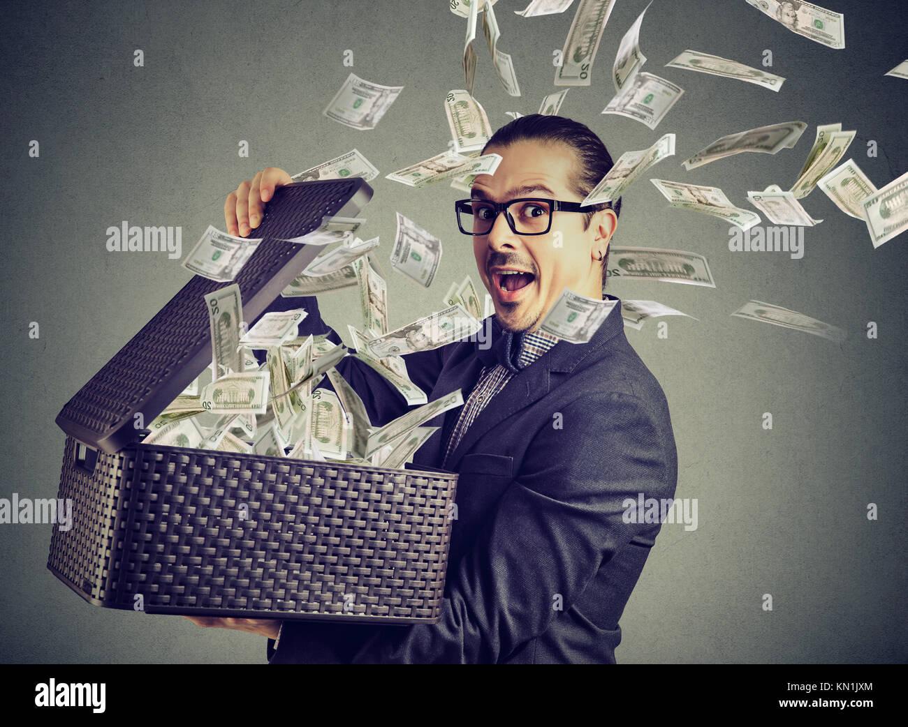 Erfolgreicher Geschäftsmann Öffnen einer Box mit Geld weg fliegen aufgeregt Stockbild