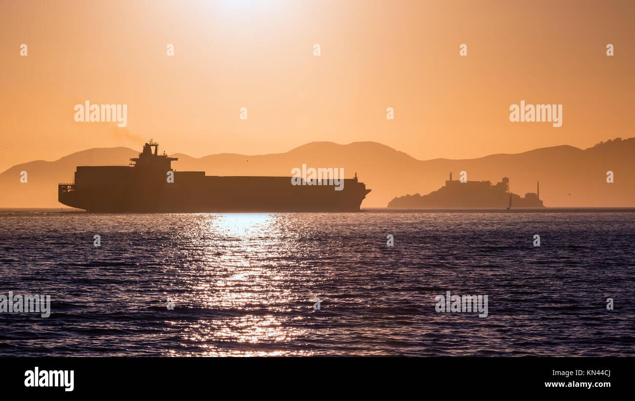 Die Insel Alcatraz Gefängnis bei Sonnenuntergang und Handelsschiff in San Francisco, Kalifornien, USA. Stockbild