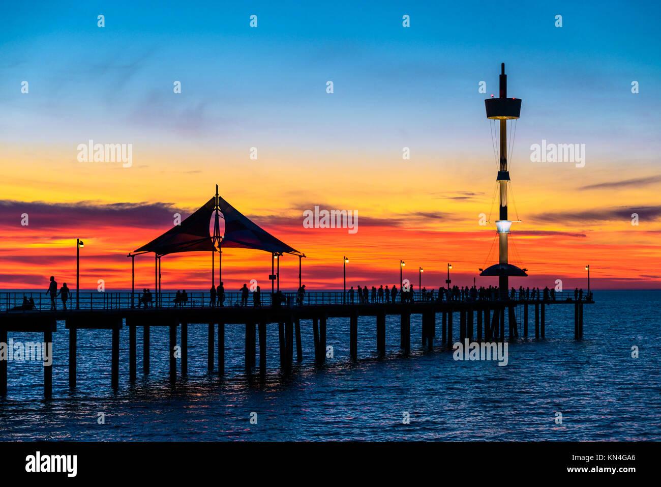 Menschen zu Fuß entlang der Brighton Pier bei Sonnenuntergang. South Australia Stockbild
