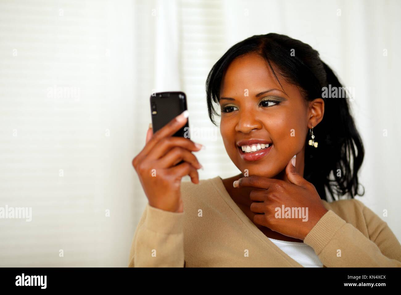 Porträt einer anspruchsvollen Frau liest eine Nachricht auf Handy. Stockbild