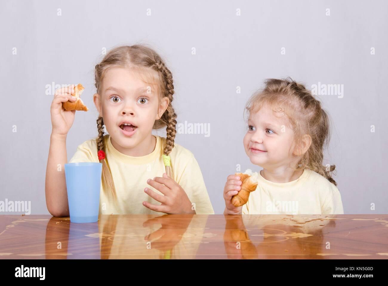 zwei kinder am tisch sitzen essen ein muffin und trinken von farbigen plastikbechern stockfoto. Black Bedroom Furniture Sets. Home Design Ideas