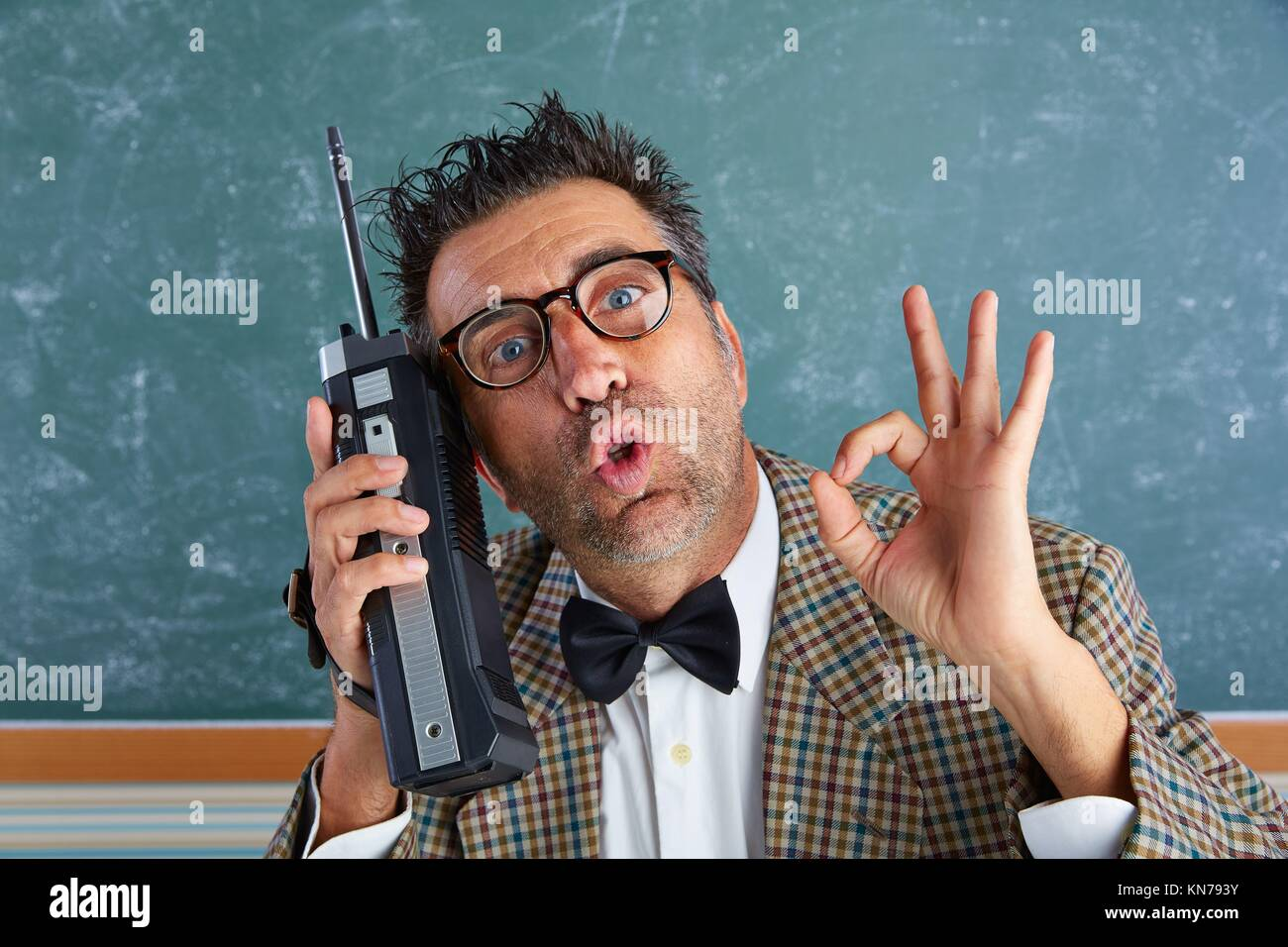 Nerd dumme Privatdetektiv mit retro Walkie talkie auf Lehrer balckboard. Stockbild