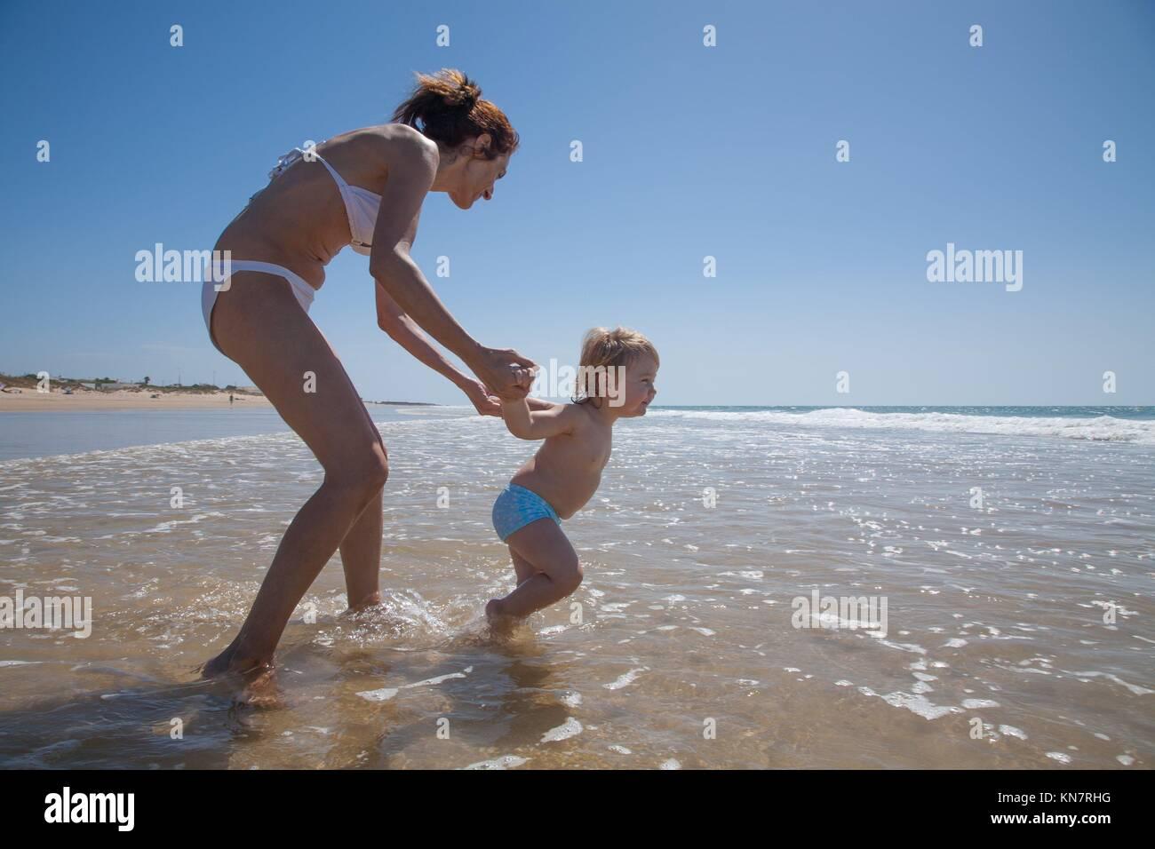 Sommerurlaub mit der Familie von zwei Jahren blond Baby brave mit blauen Badeanzug zu Fuß und ziehen Frau Mutter Stockbild